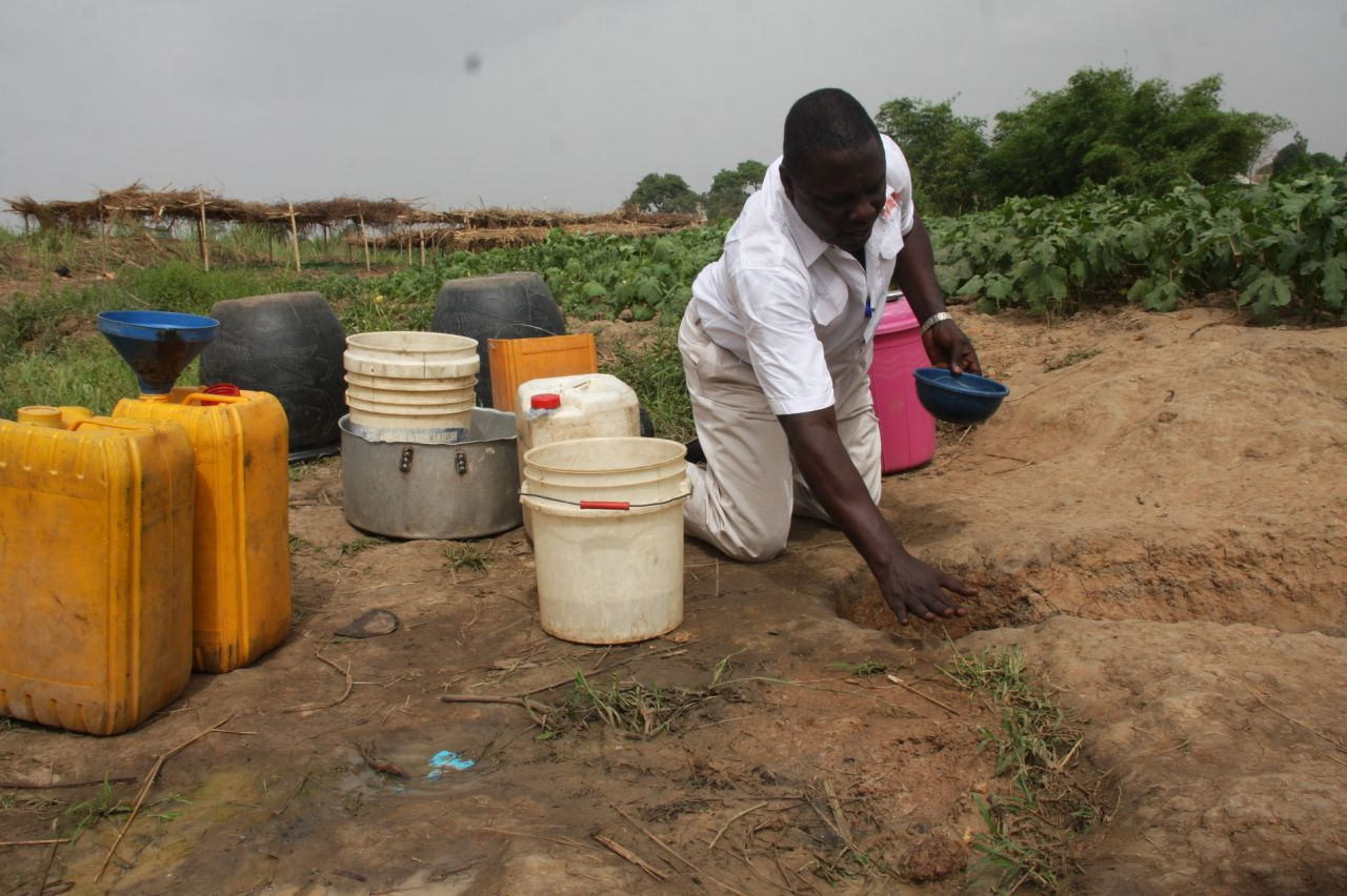 Olufemi Aduwo,President,Rights Monitoring Group helping the people to fetch water during RMG/CCDI SDGs assessment exercise in the State in 2016.